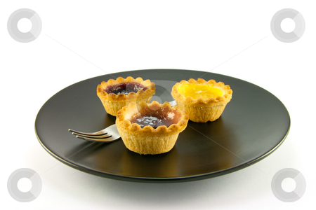 Three Jam Tarts stock photo, Three red and yellow small pastry jam tarts on a black plate with a fork on a white background by Keith Wilson