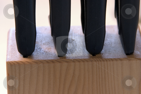 Knives in Wood Block stock photo, Close up on a wooden block that stores knives by Mehmet Dilsiz
