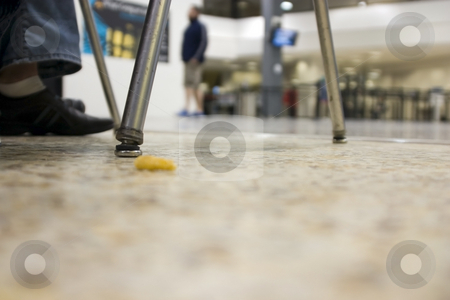 Floor view with a dropped snack at an airport stock photo, Floor view with a dropped onion ring at an airport by Mehmet Dilsiz