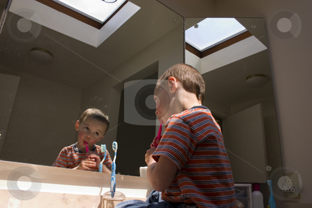 Little Boy Brushing his Teeth in Front of a Mirror stock photo, Little Boy Brushing his Teeth in Front of a Mirror sitting on the counter by Mehmet Dilsiz