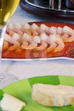 Close up on sliced bread on a table stock photo, Close up on a plate of shrimps with sliced bread and a glass of wine on the foreground by Mehmet Dilsiz