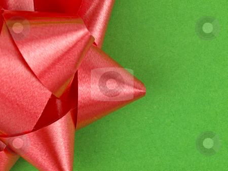 Close up of red bow stock photo, Close up of red bow on green wrapping paper by John Teeter