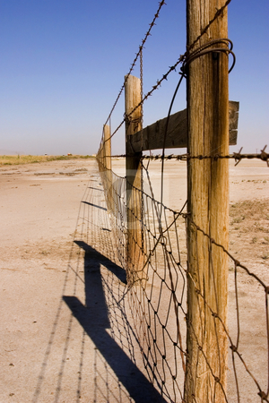 Wire and Wooden Fence Under Clear Skies stock photo, Fence in the Sale Lake in Summer in Utah with Clear Blue Skies by Mehmet Dilsiz