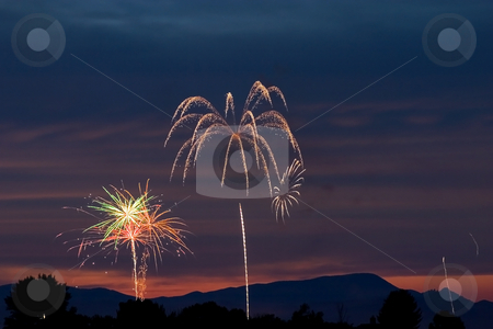 Firecrackers In The Sky During Sunset stock photo, Firecrackers During Fourth of July - New Years Eve by Mehmet Dilsiz