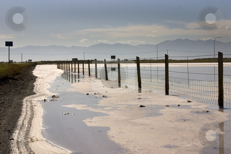 Fence in the Salt lake stock photo, Fence in the Salt Lake in Summer in Utah with Clear Blue Skies by Mehmet Dilsiz