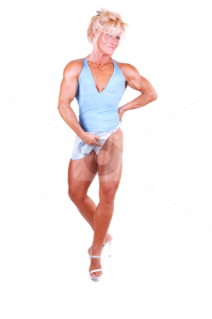 Bodybuilding woman. stock photo, A blond muscular bodybuilding girl standing in the studio shooing her  strong legs in high heels and lifting the short skirt, over white background. by Horst Petzold