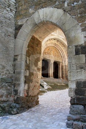 Carennac Tympanum stock photo, Looking through an archway entrance to the cloisters at the main priory door with its 12thC carved tympanum  in Carennac, Lot, France. Carennac is officially listed as one of the 152 ???most beautiful villages of France???/ ???plus beaux villages de France???. by Gozzoli
