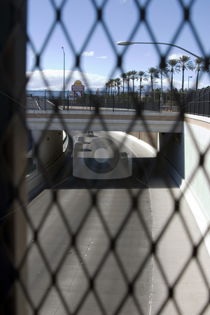 Highway Behind the Fences in Las Vegas  stock photo, Highway Behind the Fences in Las Vegas -Road in focus by Mehmet Dilsiz