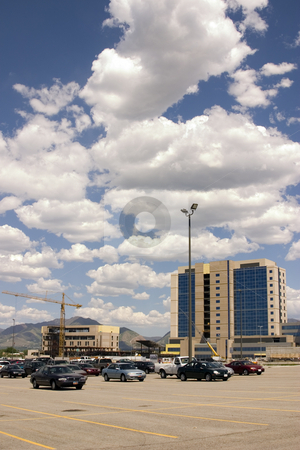 Construction and the Parking Lot stock photo, Mirrored Construction Buildings and the Parking Lot with the Clouds in the Skies by Mehmet Dilsiz