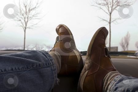 Feet on the Dashboard Relaxing stock photo, Feet on the dashboard relaxing during lunch with trees on the background by Mehmet Dilsiz
