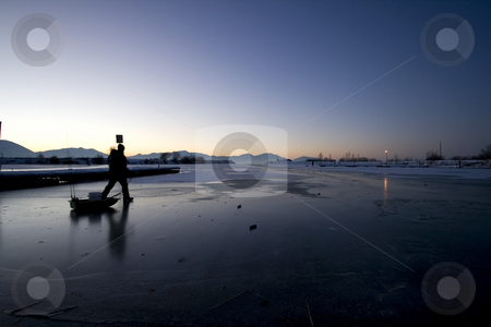 Fisherman Walking on Ice to Catch Fish stock photo, Early in the Morning a Fisherman Walking on Ice to Catch Fish by Mehmet Dilsiz