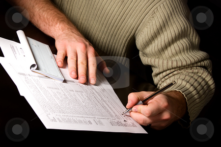 Signing the Tax Forms stock photo, A man signing 1040 tax forms by Mehmet Dilsiz