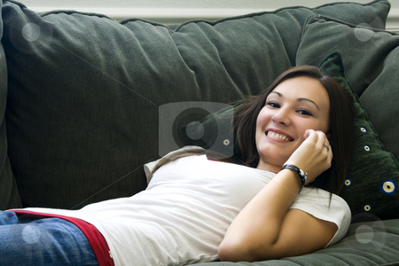 Teenager Talking on the Cell Phone  stock photo, Teenager Talking on the Cell Phone on a Green Couch by Mehmet Dilsiz