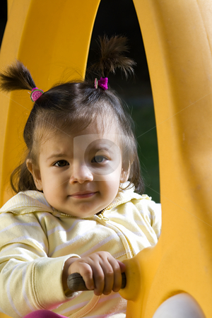 Little Girl on the Swing stock photo, Little Girl Looking at the Camera from the Swing by Mehmet Dilsiz