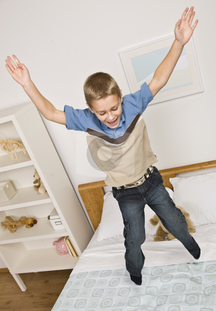 Boy Jumping on Bed stock photo, A young boy is jumping up and down and his bed.  He is smiling and looking away from the camera.  Vertically framed shot. by Jonathan Ross