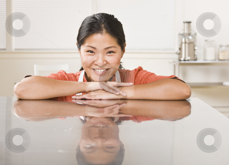 Woman Leaning on Counter stock photo, A woman is leaning on a clean kitchen counter.  Horizontally framed shot. by Jonathan Ross