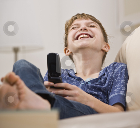 Girl Holding Cellphone stock photo, A young girl is holding a cell phone, looking away from the camera, and laughing.  Horizontally framed shot. by Jonathan Ross