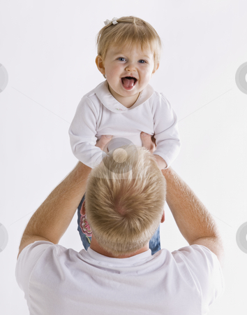 Father Holding Daughter stock photo, A young father is holding up his baby daughter.  She is smiling at the camera.  Vertically framed shot. by Jonathan Ross
