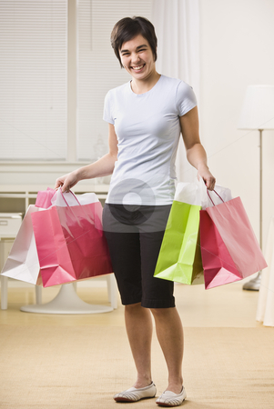 Woman with Shopping Bags stock photo, A young woman is holding multiple shopping bags and smiling at the camera.  Vertically framed shot. by Jonathan Ross