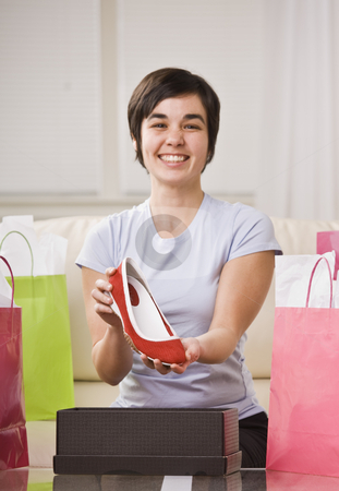 Girl Holding up Shoe stock photo, A young lady is holding up a shoe from a box and smiling at the camera.  She is surrounded by shopping bags.  Vertically framed shot. by Jonathan Ross