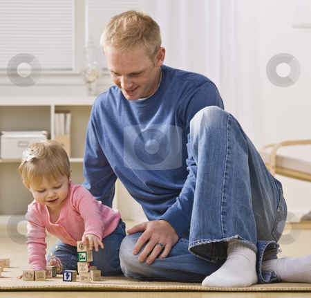 Man Playing with Daughter stock photo, A young father is on the floor playing with his daughter.  He is smiling and looking at her.  Square framed shot. by Jonathan Ross