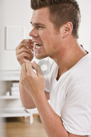 Man Flossing Teeth stock photo, A man is standing in front of a mirror and flossing his teeth.  Vertically framed shot. by Jonathan Ross