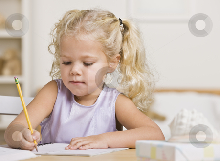 Girl Writing in a Notebook stock photo, A young girl is writing in a notebook.  She is looking away from the camera.  Horizontally framed shot. by Jonathan Ross