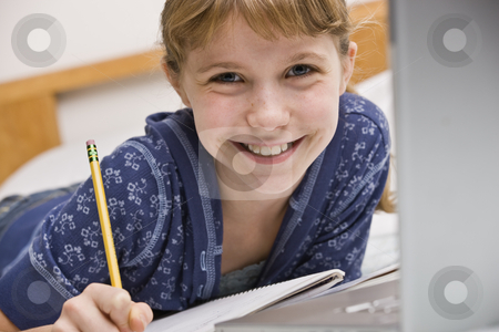 Girl Working on Homework stock photo, A young girl is seated at a computer desk and is working on her homework.  She is smilng at the camera.  Horizontally framed shot. by Jonathan Ross
