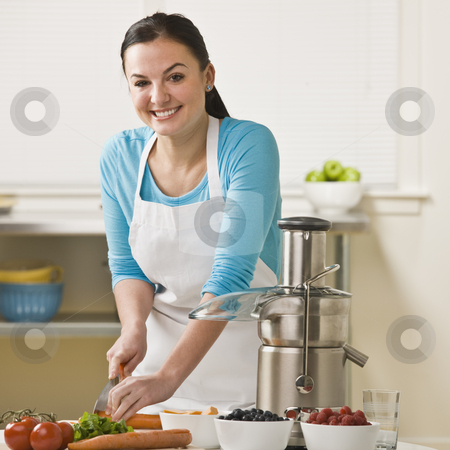 Women Slicing Produce stock photo, A woman is in the kitchen and slicing produce for the juicer.  She is smiling at the camera.  Square framed shot. by Jonathan Ross