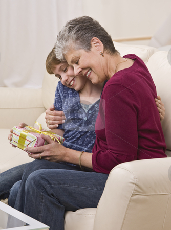 Grandma and Granddaughter with Present stock photo, A grandmother hugs her granddaughter while holding a present. They are seated on a sofa and are smiling.  Vertically framed shot. by Jonathan Ross