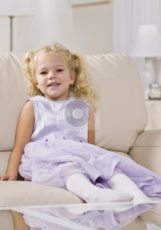 Girl Sitting on Couch stock photo, A young girl is sitting on a couch in a living room and smiling at the camera.  Vertically framed shot. by Jonathan Ross