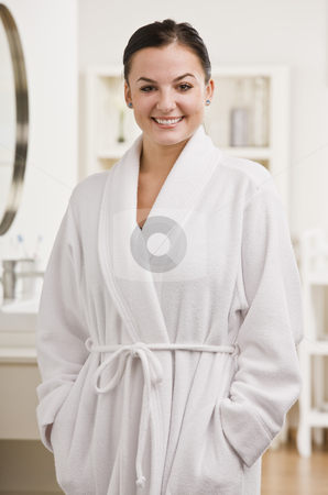 Woman Standing in Bathrobe stock photo, A woman is standing in bathrobe and smiling at the camera.  Vertically framed shot. by Jonathan Ross