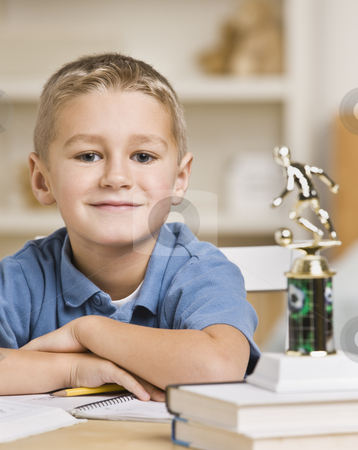 Boy Sitting in Front of Soccer Trophy stock photo, A young boy is seated at a desk with a stack of books and a trophy.  He is smiling at the camera.  Vertically framed shot. by Jonathan Ross