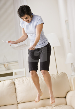 Excited Woman Jumping on Couch stock photo, An excited young woman is reading a piece of paper and jumping up and down on the couch.  She is looking away from the camera.  Vertically framed shot. by Jonathan Ross