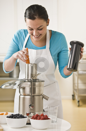 Woman Using Juicer stock photo, A young woman is using a juicer in a kitchen.  Vertically framed shot. by Jonathan Ross