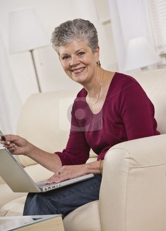 Woman on Laptop stock photo, A woman is seated on a living room sofa and working on a laptop.  She is smiling at the camera.  Vertically framed shot. by Jonathan Ross