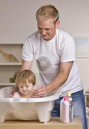 Father Giving Daughter Bath stock photo, A young father is giving his baby daughter a bath in a childs tub.  He is smiling and looking down at his daughter.  Vertically framed shot. by Jonathan Ross