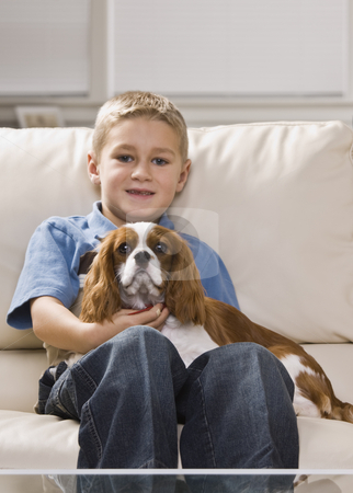 Cute Little Boy with Dog stock photo, A cute little boy holding a dog on his lap.  He is smiling.  Vertically framed shot. by Jonathan Ross