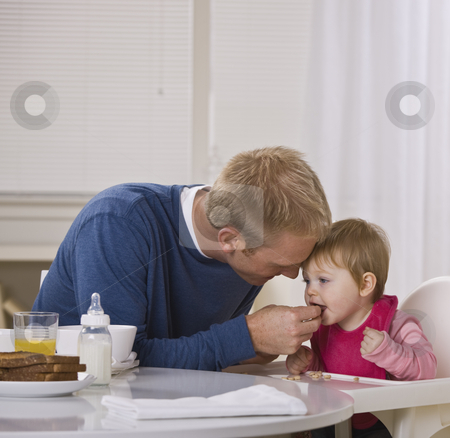 Father Feeding Daughter Breakfast stock photo, A young father feeding his daughter cereal at a breakfast table.  They are looking away from the camera. Square framed shot. by Jonathan Ross