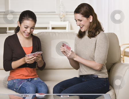 Mother and Daughter Playing Cards stock photo, A mother and her daughter are seated on the living room sofa and are playing cards together.  They are smiling and looking away from the camera.  Horizontally framed shot. by Jonathan Ross