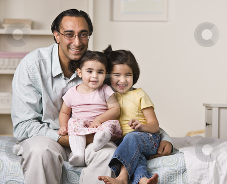 Father Sitting with Daughters stock photo, A father is sitting on a bed with his two young daughters.  They are smiling at the camera.  Horizontally framed shot. by Jonathan Ross