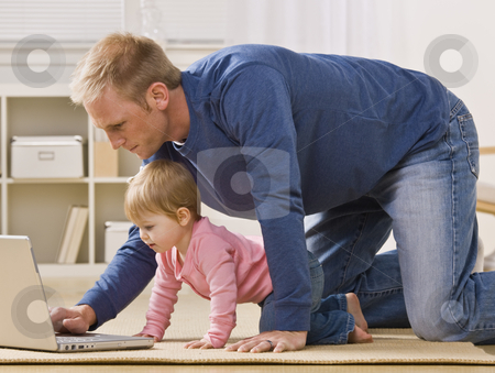 Father and Daughter with Laptop stock photo, A father uses a laptop while his baby daughter watches.  Both are on all fours in their living room.  Horizontally framed shot. by Jonathan Ross