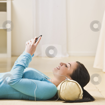 Woman With MP3 Player stock photo, A young woman is lying on the floor and listening to an mp3 player.  She is smiling and looking away from the camera.  Square framed shot. by Jonathan Ross