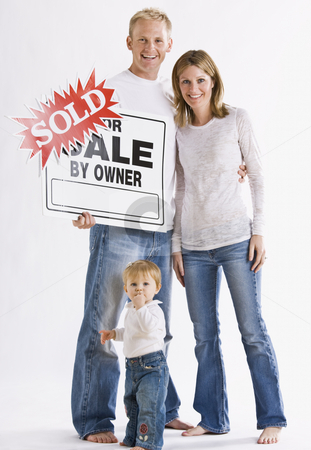 Family in Front of Sign stock photo, A young family is standing in front of a For Sale Sign and are smiling at the camera.  Vertically framed shot. by Jonathan Ross