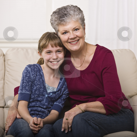 Grandmother Hugging Granddaughter stock photo, A grandmother is sitting on a couch and hugging her granddaughter.  They are smiling at the camera.  Square framed shot. by Jonathan Ross