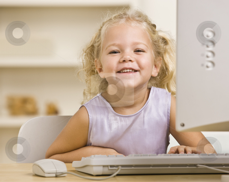 Girl on Computer stock photo, A young girl is seated at a computer desk and smiling at the camera.  Horizontally framed shot. by Jonathan Ross