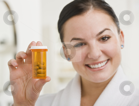 Woman Holding up Medication stock photo, A woman is holding up a bottle of prescription medication and smiling at the camera.  Horizontally framed shot. by Jonathan Ross