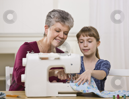 Grandmother Sewing with Granddaughter stock photo, A grandmother and granddaughter using a sewing machine together. Horizontally framed shot. by Jonathan Ross