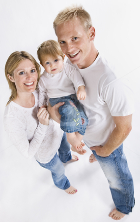 Family Smiling at Camera stock photo, A young family is wearing white T-shirts and smiling up at the camera.  Vertically framed shot. by Jonathan Ross