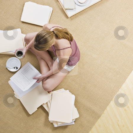 Woman Looking through Files stock photo, A woman is seated on the floor, looking through files, and drinking coffee.  Square framed shot. by Jonathan Ross